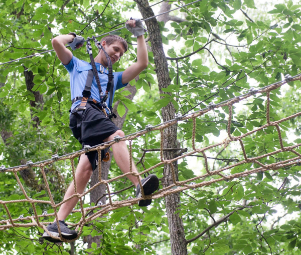 Boy climbing obstacle at Treetop Adventure